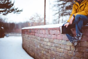 Teen sitting on wall with Bible